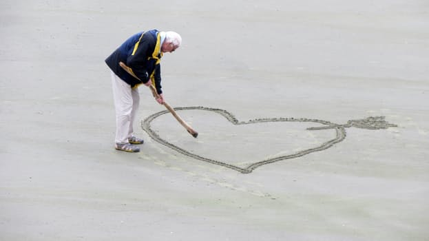 An old man writing a heart on the ground