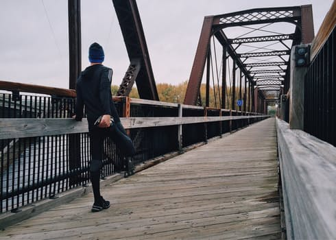 A young man trying to run is on the bridge